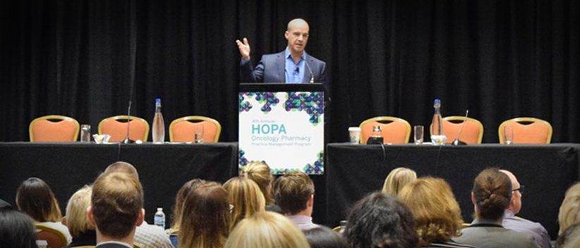 HOPA Pharmacy PMP image of male speaker at podium